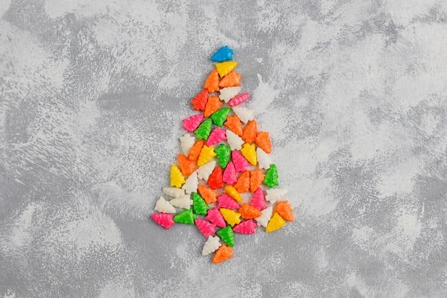 Błyszczące cukierki w kształcie choinki na szarym stole. widok z góry, leżał płasko