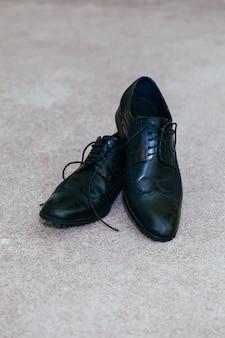 Błyszczące czarne buty męskie dla panny młodej, leżące na podłodze męskie buty leżą na podłodze