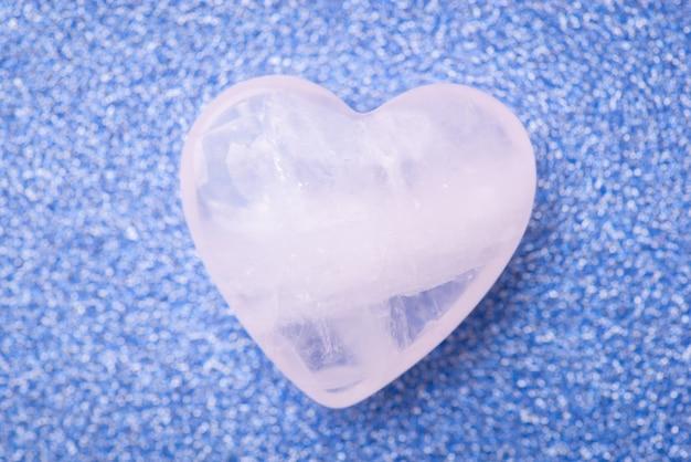 Błyszczące kamienne serce na niebieskim tle