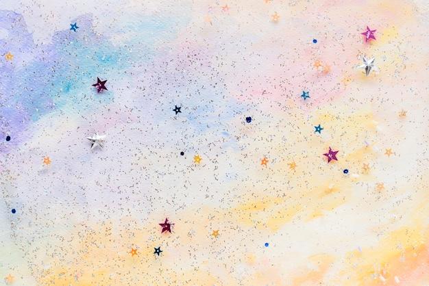 Błyszczące konfetti gwiazd na kolorowe abstrakcyjne pastelowe tło akwarela