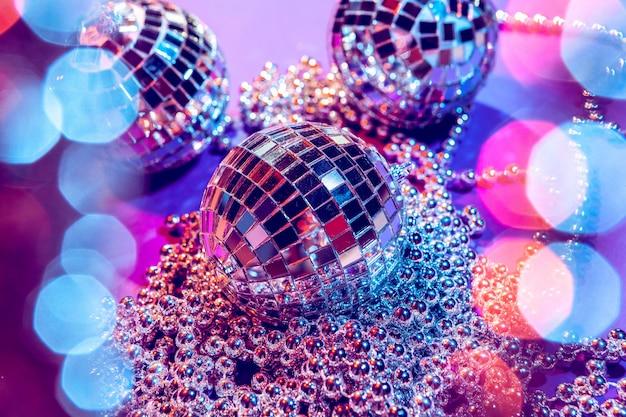 Błyszczące małe kule disco błyszczące w pięknym fioletowym świetle.
