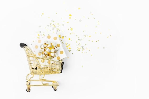 Błyszczące ozdoby świąteczne i prezenty ze złotymi kokardkami w koszyku na białym tle. koncepcja zakupów świątecznych. płaski układanie, widok z góry