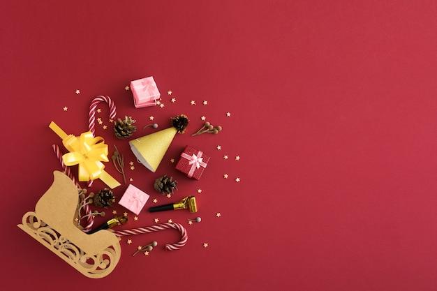 Błyszczące ozdoby świąteczne i sanie świętego mikołaja na czerwonym tle. koncepcja zakupy i prezenty. koncepcja zakupów świątecznych. płaski układanie, widok z góry