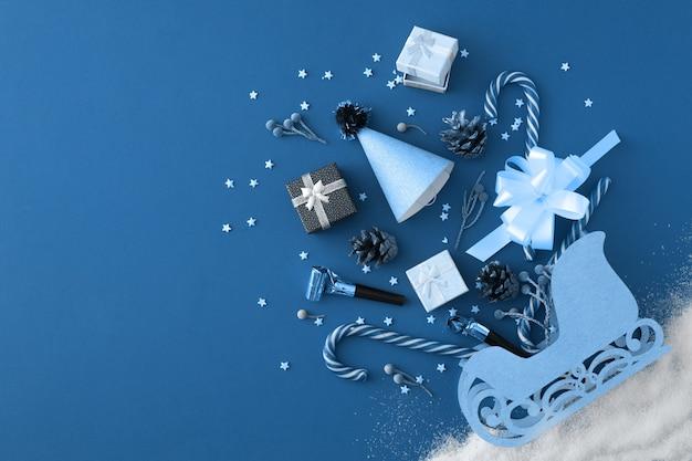 Błyszczące ozdoby świąteczne i sanie świętego mikołaja na klasycznym niebieskim tle. koncepcja zakupy i prezenty. koncepcja zakupów świątecznych. płaski układanie, widok z góry