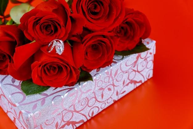 Błyszczące pudełko i pierścionek z pięknymi czerwonymi różami na czerwonym tle. koncepcja walentynki.