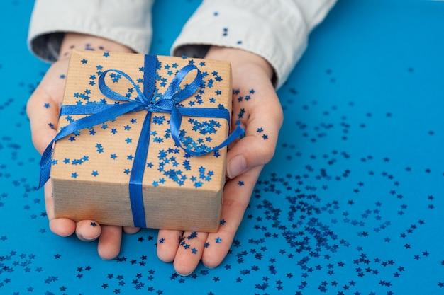 Błyszczące pudełko upominkowe zawinięte w papier rzemieślniczy i przewiązane kokardą w dłoniach dziecka
