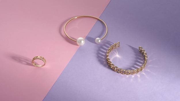 Błyszczące złote bransoletki i pierścionek w kształcie łańcuszka na różowym i fioletowym tle