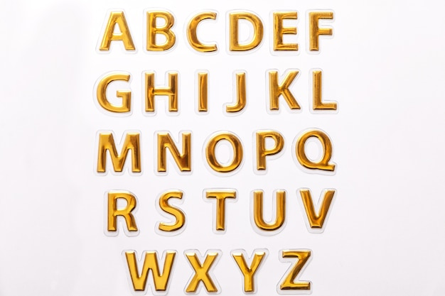 Błyszczące złote litery na białym tle