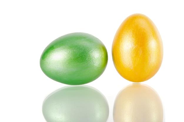 Błyszczące żółte i zielone jajko na białym tle