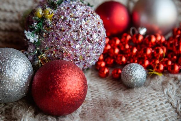 Błyszczący brokatowy wybór bombek. czerwone i srebrne bombki sznureczek na dzianinie z teksturą. koncepcja dekoracji nowego roku i świąteczny nastrój.