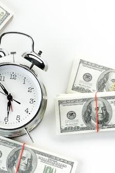 Błyszczący budzik i stosy banknotów dolara