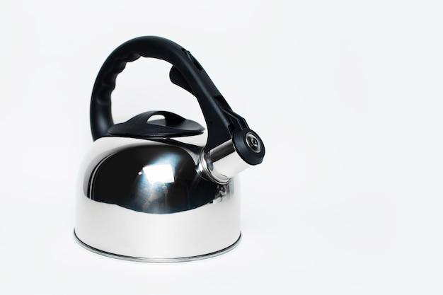 Błyszczący czajniczek z czarną rączką na białym tle. zdjęcie studyjne.