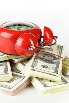 Błyszczący czerwony budzik i stosy banknotów dolara i euro