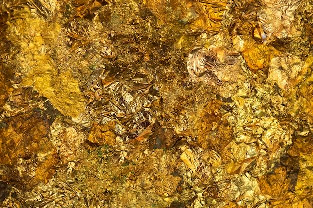 Błyszczący liść żółtego złota lub resztki złotej folii tła