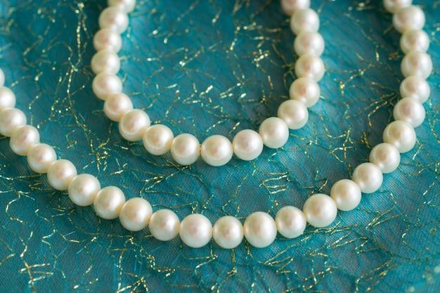 Błyszczący naszyjnik z naturalnych pereł na turkusowym jedwabiu.