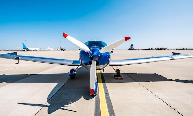 Błyszczący niebieski samolot sportowy na pasie startowym