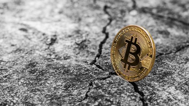 Błyszczący złoty bitcoin na popękanej podłodze.