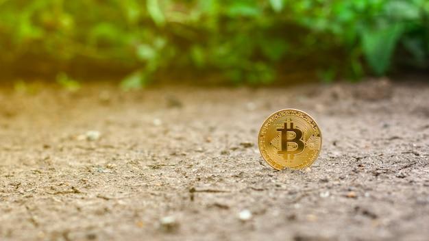 Błyszczący złoty bitcoin na ziemi.