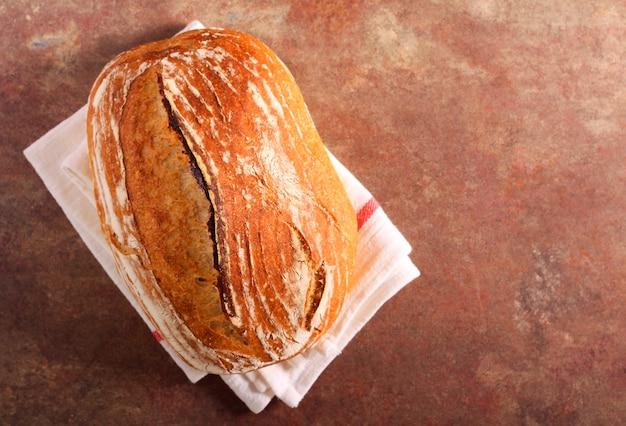 Bochenek białego chleba na zakwasie, na kamiennej powierzchni