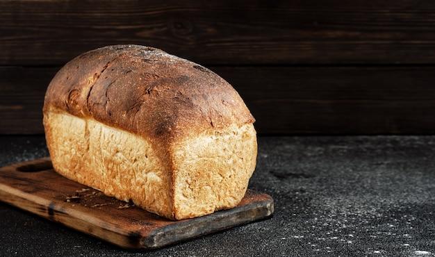 Bochenek białego chleba rustykalnego z bliska na drewnianej desce po pieczeniu