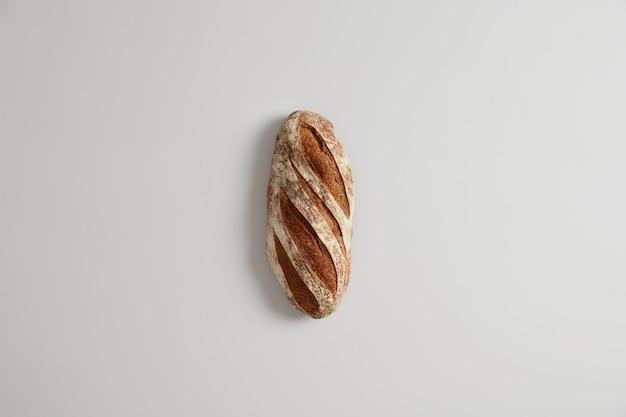 Bochenek białego, długiego chleba na zakwasie i organicznej mące, odizolowany. domowa koncepcja pieczenia. zdrowe odżywianie. produkt węglowodanowy. jedzenie i konsumpcjonizm. widok z góry. selektywna ostrość.