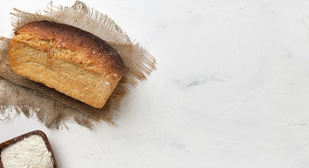 Bochenek białego rustykalnego chleba na lnianej podszewce na białym stole. pomysł na mały biznes, wypiek zdrowego chleba na zakwasie na zamówienie. widok z góry z miejscem na kopię