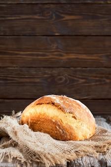 Bochenek chleba domowego białego mleka na zakwasie, selektywne focus. close-up, z miejsca na kopię. wypiekaj chleb na wyściółce z tkaniny, na drewnianej ścianie