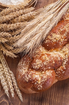 Bochenek chleba i kłosy pszenicy rie na vintage pokładzie