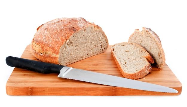 Bochenek chleba i nóż na białym tle