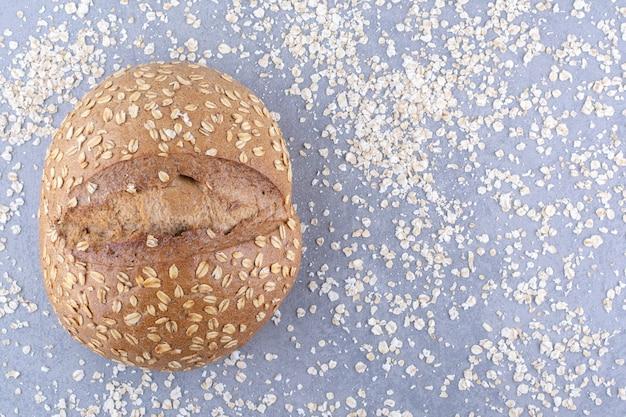 Bochenek chleba leżący w rozsypanej mieszaninie płatków na marmurowej powierzchni