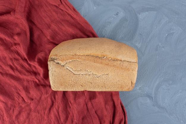 Bochenek chleba na czerwonym obrusie na marmurowym stole.