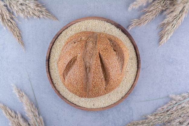 Bochenek chleba na tacy wypełnionej sezamem otoczonym suszonymi łodygami trawy piórkowej na marmurowej powierzchni