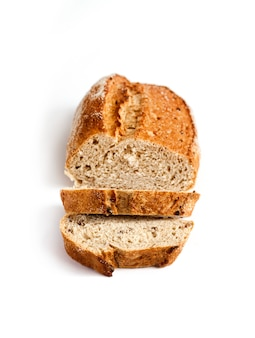 Bochenek chleba pełnoziarnistego z plastrami na białym tle