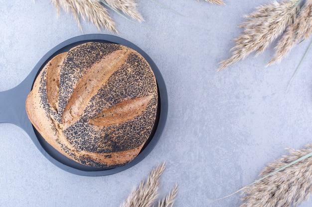 Bochenek chleba pokryty czarnym sezamem na patelni, obok łodyg suszonej trawy z piór na marmurowej powierzchni