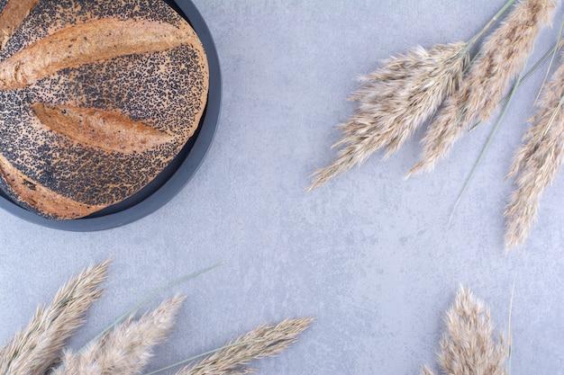 Bochenek chleba pokryty sezamem na talerzu obok łodyg suszonej trawy z piór na marmurowej powierzchni