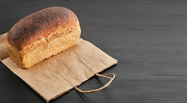 Bochenek chleba rustykalnego w papierowej torbie na czarnym drewnianym stole jest przygotowany do dostawy do kupującego
