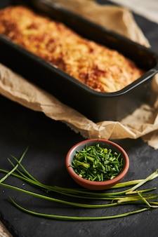 Bochenek chleba serowego z masłem ziołowym na drewnianym talerzu z ziołami