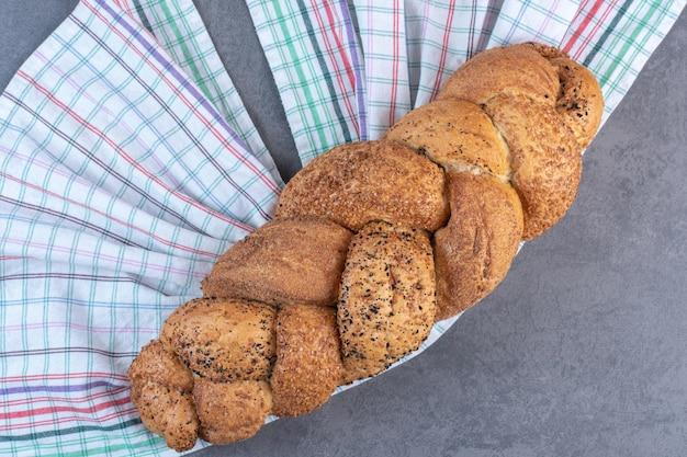 Bochenek chleba strucia na ręczniku na marmurowym tle. zdjęcie wysokiej jakości
