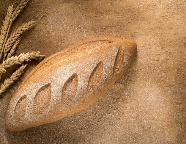 Bochenek chleba z kolcami na otynkowanej powierzchni, widok z góry