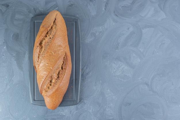 Bochenek chleba żytniego na marmurowym stole.