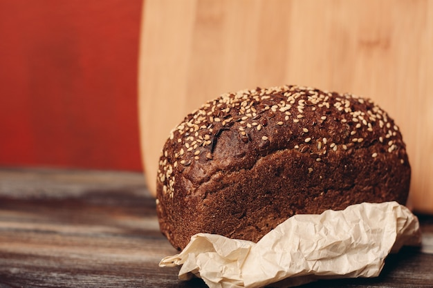 Bochenek chleba żytniego na papierowych podstawkach i deska na tle drewnianego stołu