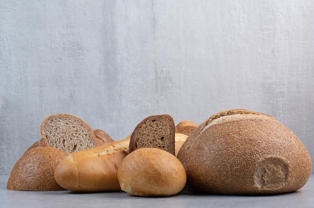 Bochenek i kromki chleba na tle marmuru. wysokiej jakości zdjęcie