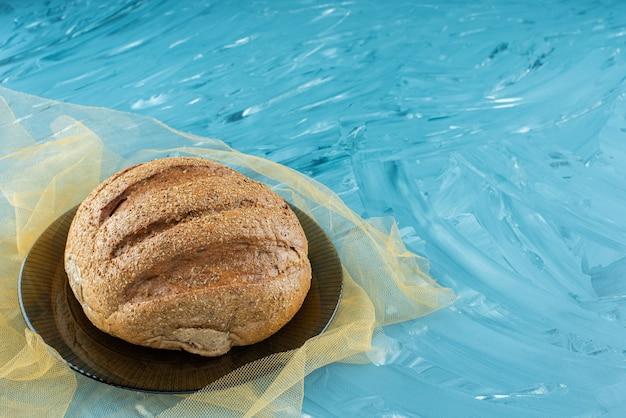 Bochenek okrągłego chleba ze skórką na szklanym talerzu.