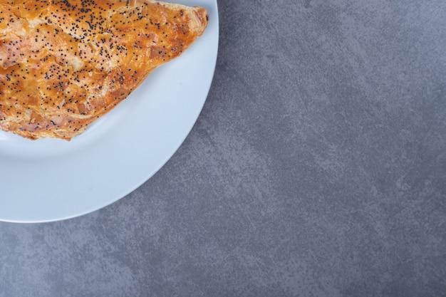 Bochenek sezamu na talerzu na marmurowym stole.