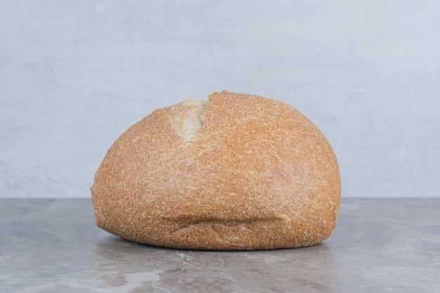 Bochenek świeżego chleba na tle marmuru.