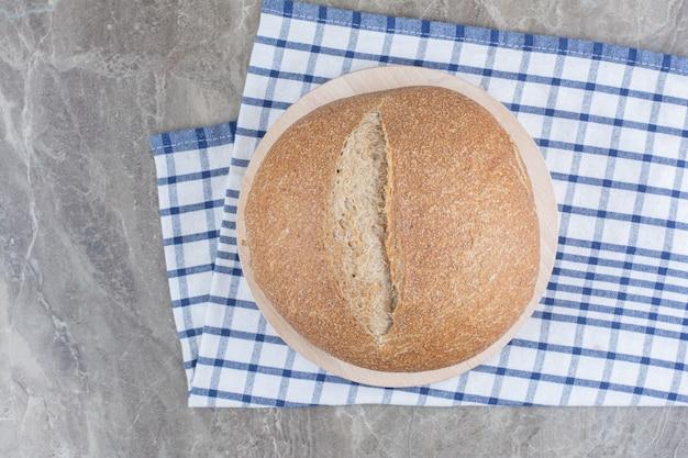 Bochenek świeżego ciemnego chleba na obrusie