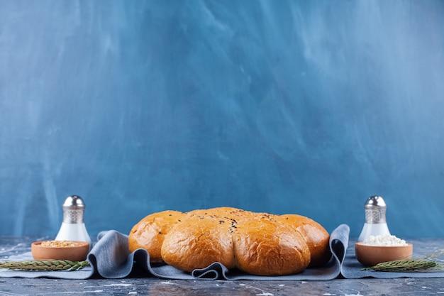 Bochenek świeżego pachnącego chleba z solą i pieprzem na niebiesko.