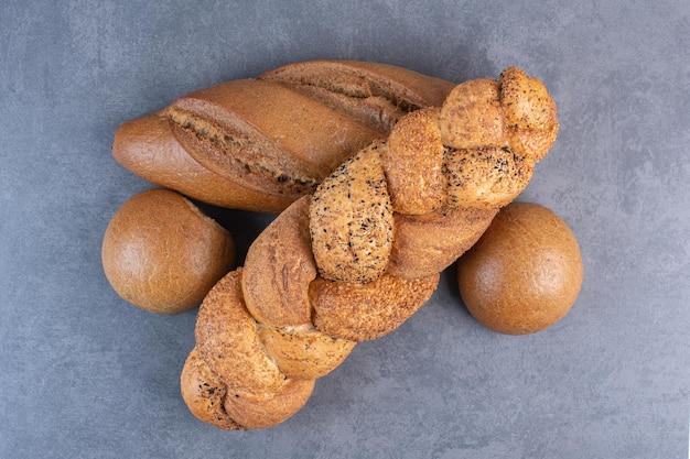 Bochenki chleba baton, strucia i bułka wiązana na marmurowym tle. zdjęcie wysokiej jakości
