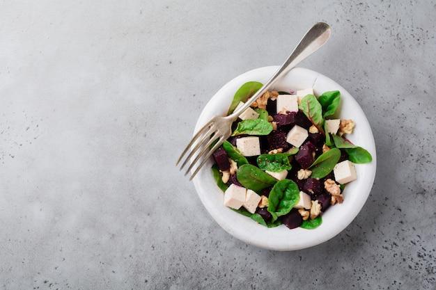 Boćwina, rukola, burak, ricotta i sałatka z orzechów włoskich z oliwą z oliwek na starym talerzu ceramicznym na szarej betonowej powierzchni