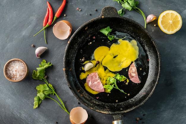 Boczek lub plastry mięsa i ziół na patelni z gorącym olejem, jajecznica